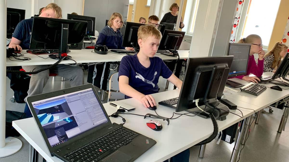 Pelisuunnittelukerholaiset istuvat tietokoneiden edessä koulun luokassa.