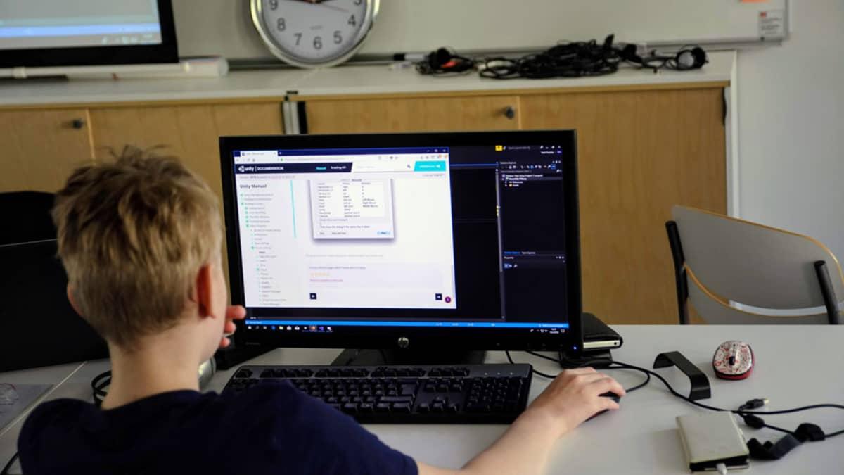 Koululainen on tietokoneen ääressä luokassa.