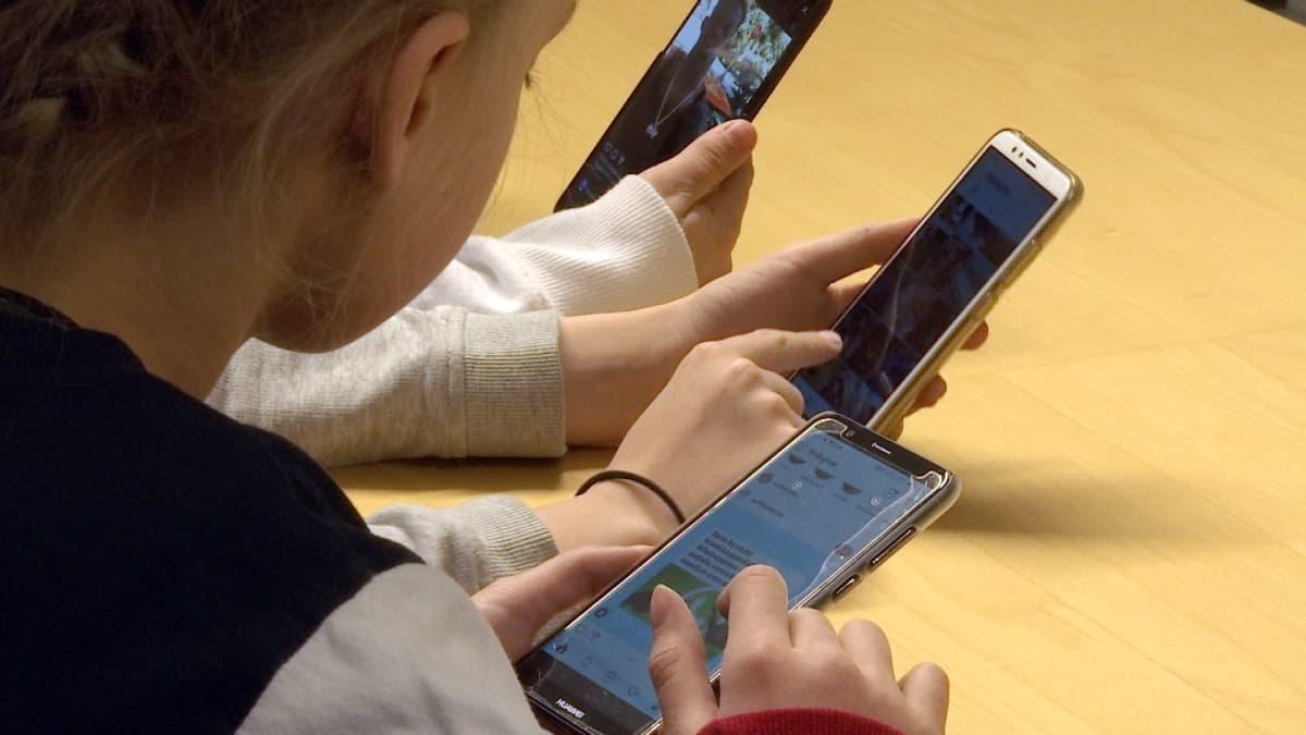 Lapset selaavat somea puhelimillaan.