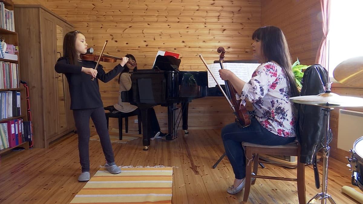 Leea Mattila harjoittelee opettajansa Niina Tuunaisen johdolla. Pianon takana säestämässä Leean äiti Kazuyo Ueno-Mattila.