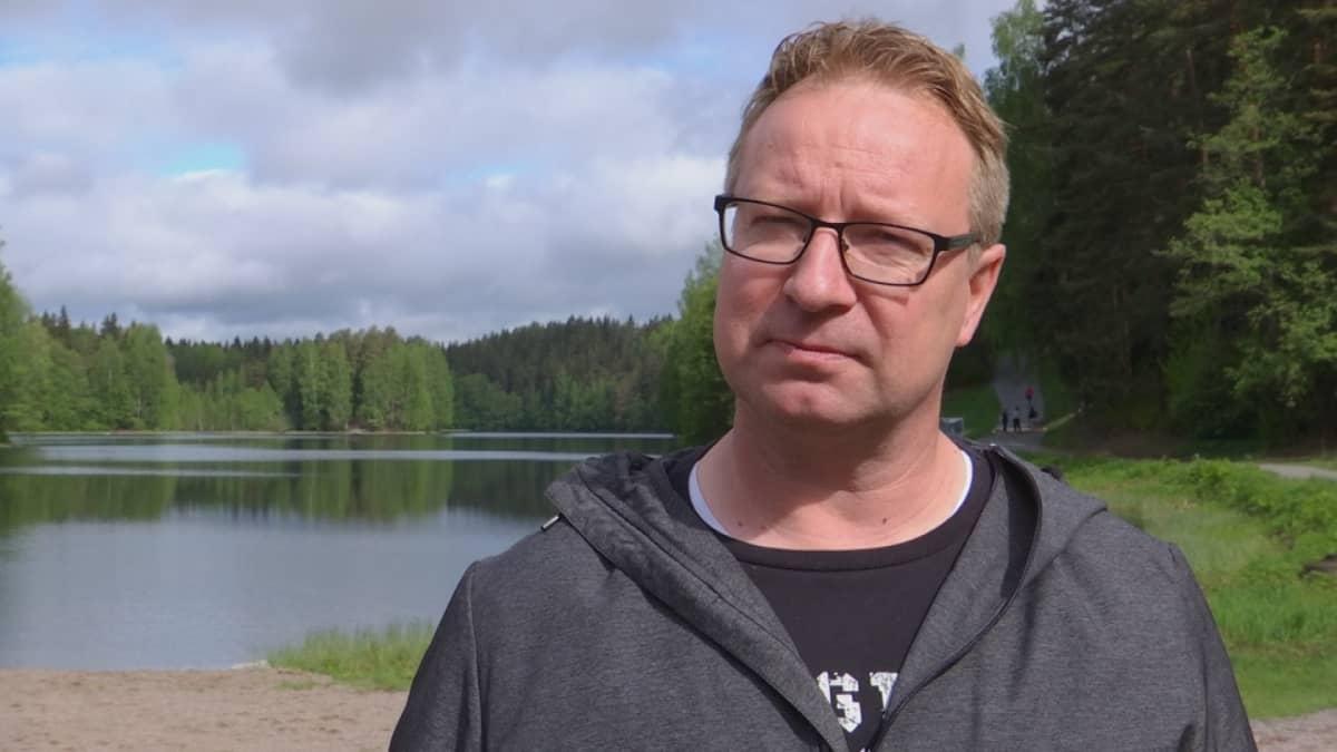 Mies seisoo järven rannassa ja katsoo kameraan.