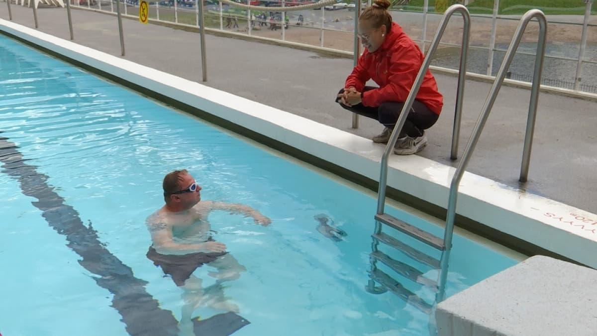 Uimaopettaja kyykistyneenä altaassa olevan uimarin viereen.