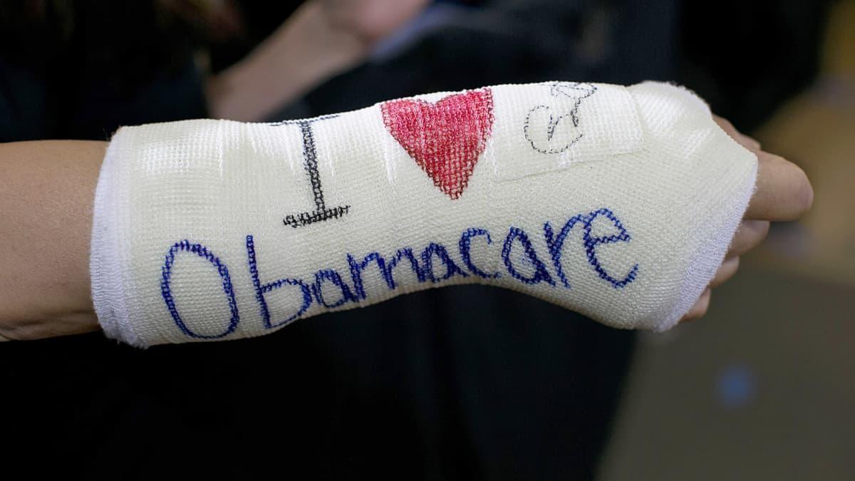 """Henkilöllä on kädessään kipsi, johon on kirjoitettu englanniksi: """"Rakastan Obamacarea"""". Rakastaa-verbi on korvattu punaisella sydänsymbolilla."""