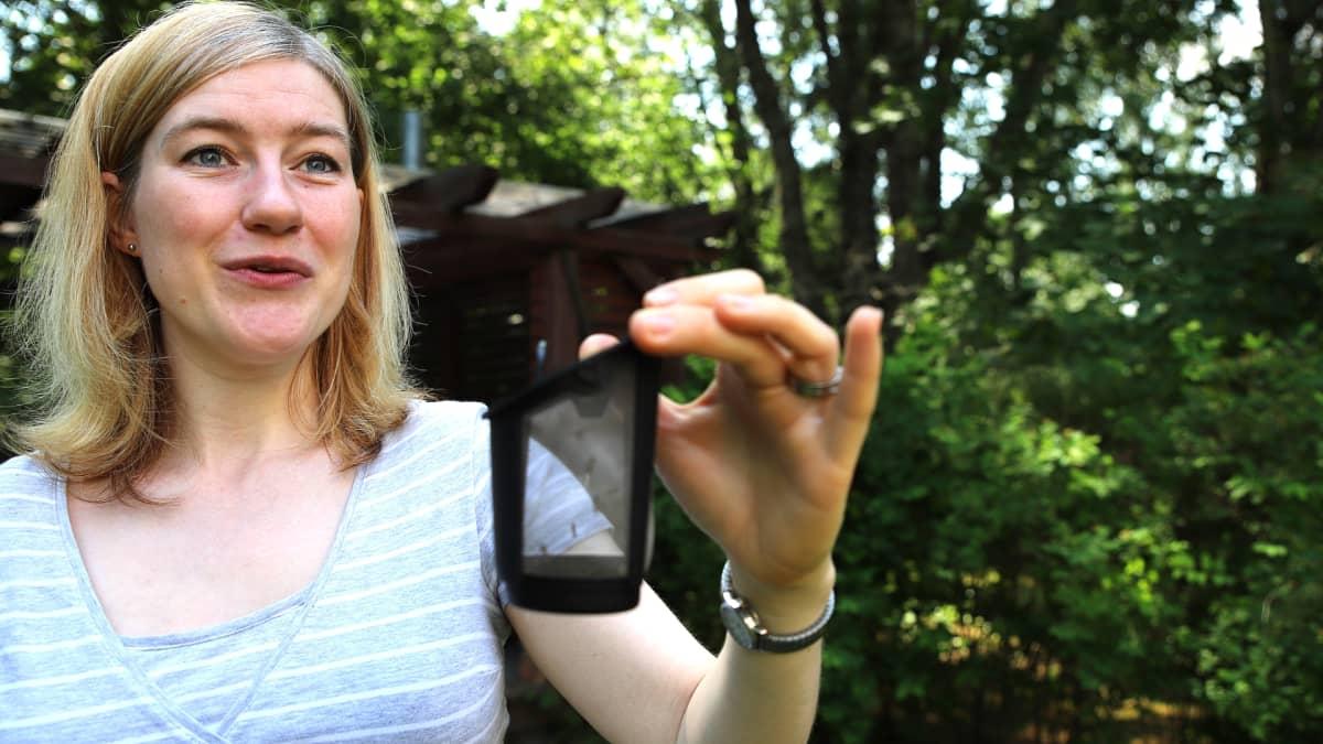 Tutkija pitää kädessään hyttysansaa, jossa on hyttysiä.
