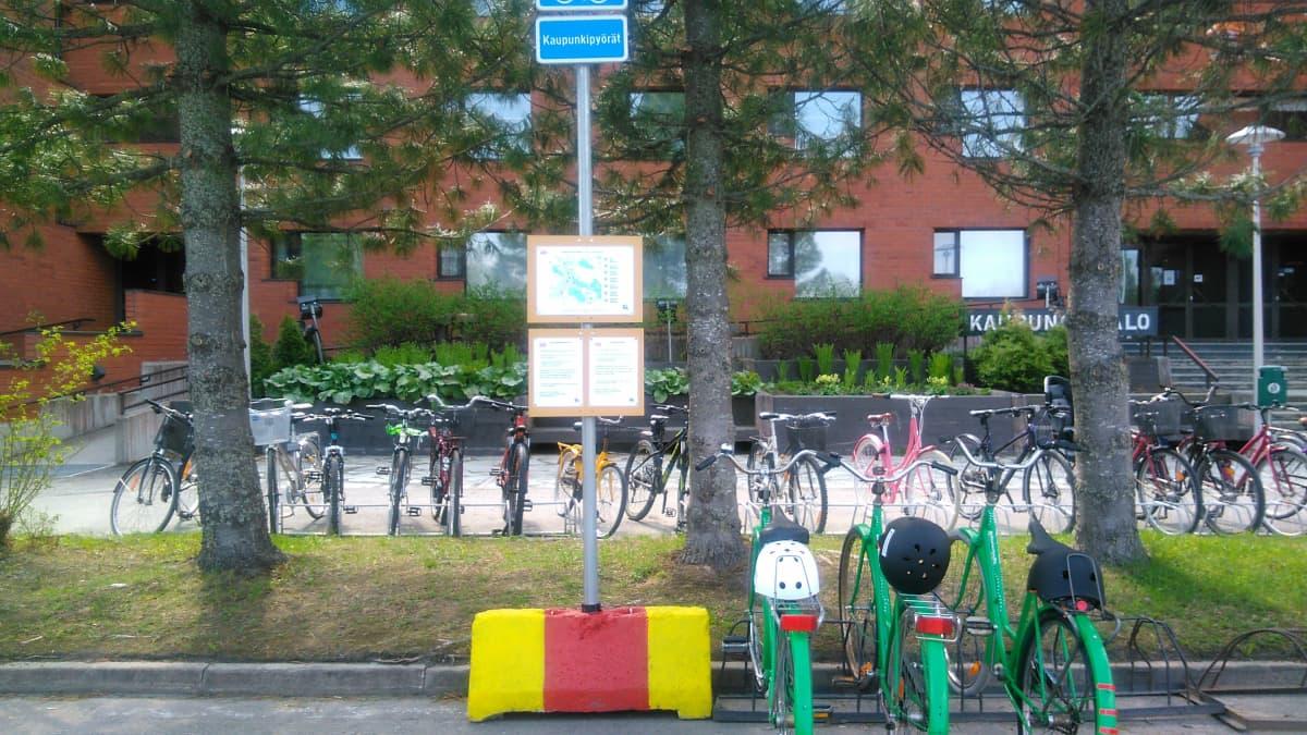 Kolme pyörää parkissa Kuusamon kaupungintalon edustalla.