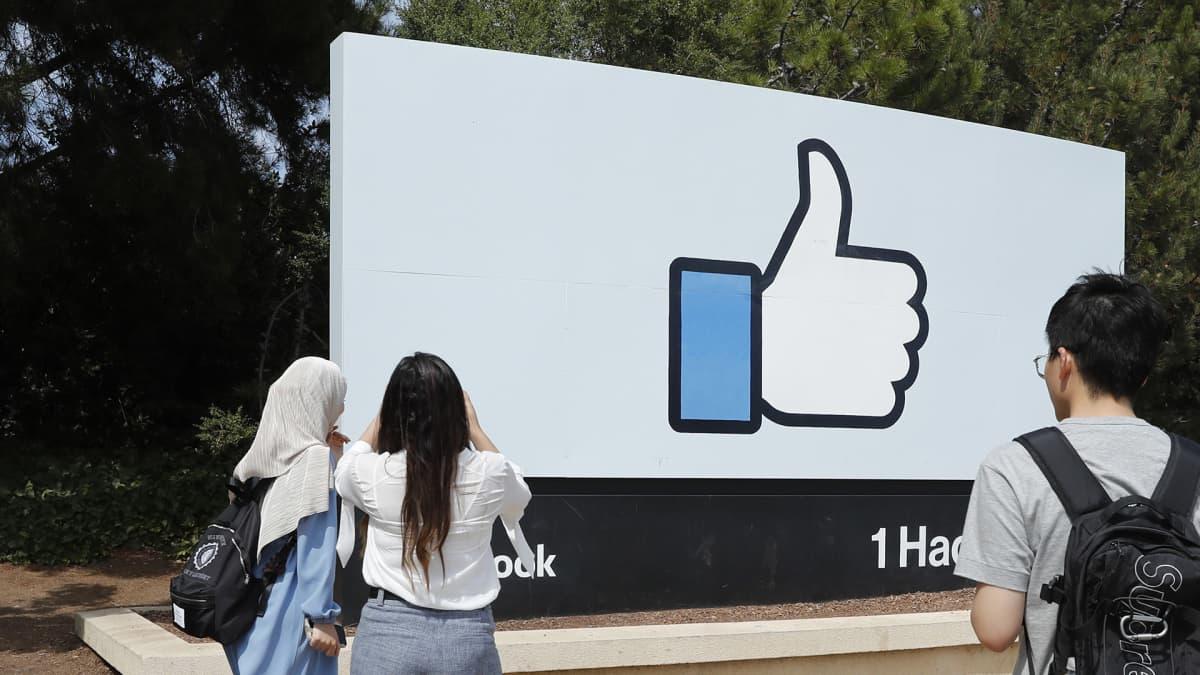 Ihmiset katselevat Facebookin tykkää peukkua Facebookin päämajan ulkopuolella.