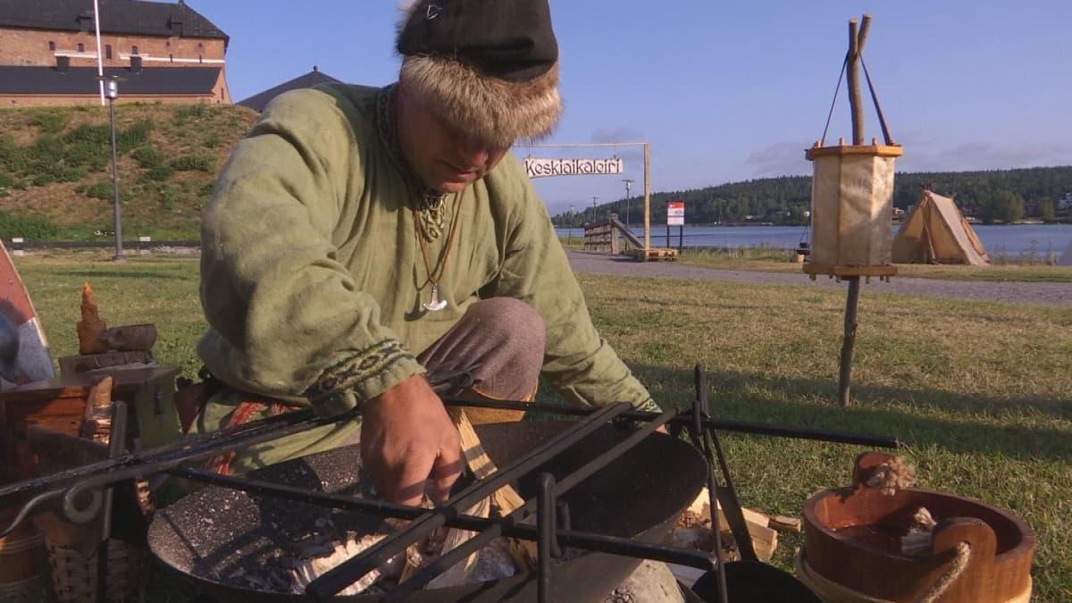 Viikinkimäiseen asuun pukeutunut miespuolinen henkilö sytyttämässä leirinsä nuotiota ennen aamupalan kokkaamista