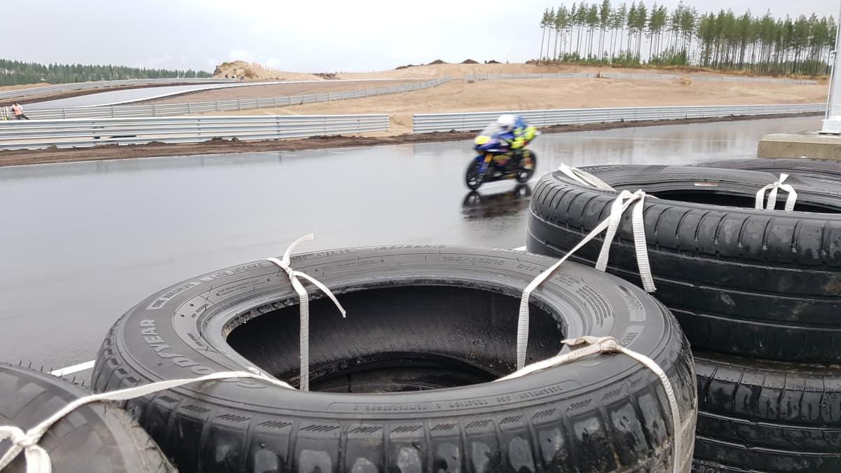 MotoGP-testikuljettaja sinikeltaisella moottoripyörällä Kymi Ringin märällä asfaltilla. Kuvattu radan reunan rengasvallin takaa.