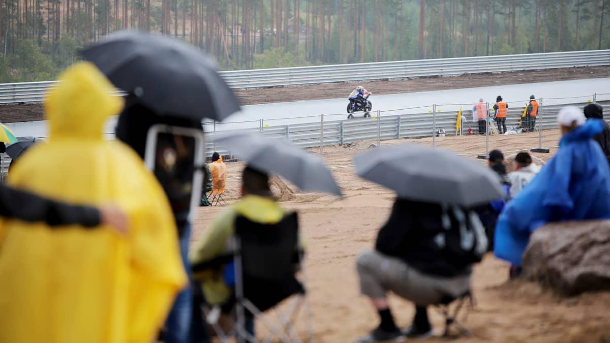 Katsojat seuvaaravat sateenvarjojen alla Kymi Ringin testiajoa