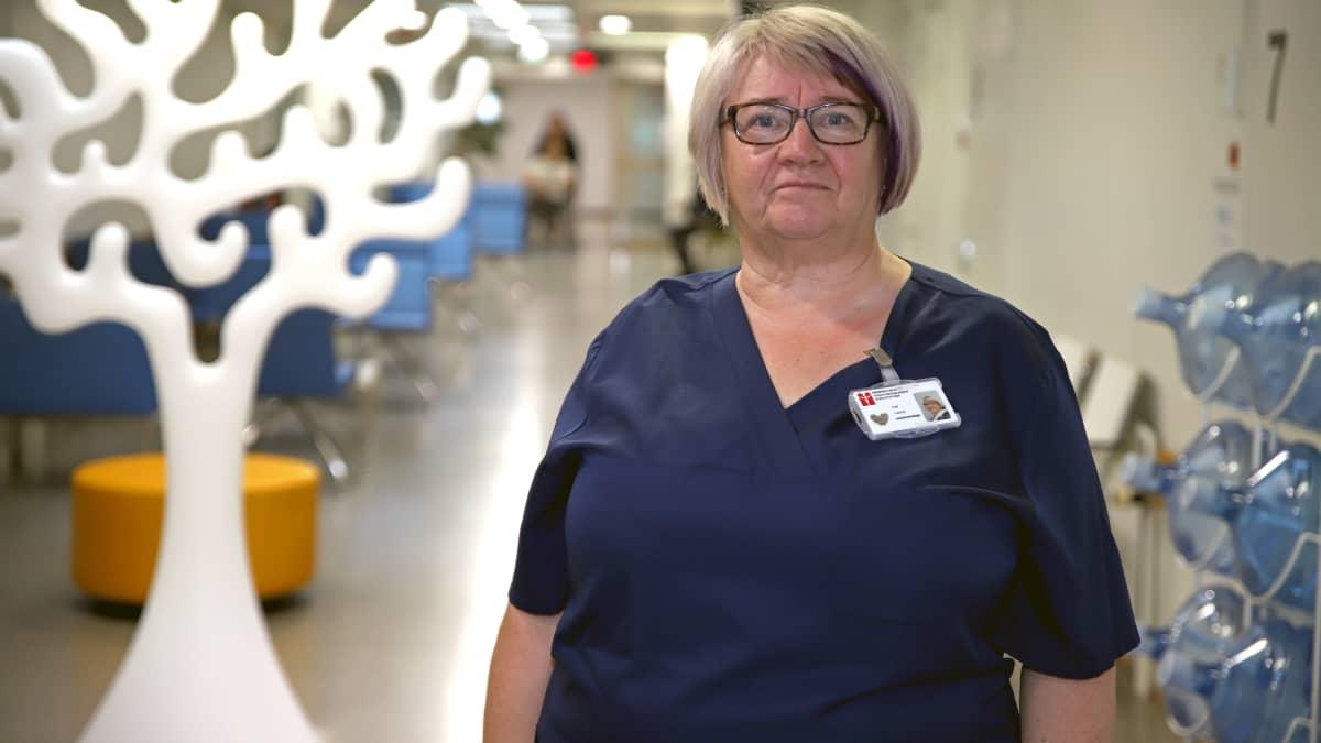 Sairaanhoitaja seisoo aulassa ja katsoo kameraan.