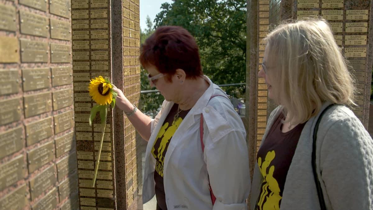 Helena Leinonen ja Maj-Lis Dahl jättävät auringonkukan Renegades-laulajan Kim Brownin haudalle (uurnalehdon muistopaasi) Hietaniemen hautausmaalla Helsingissä 1.8. 2019.