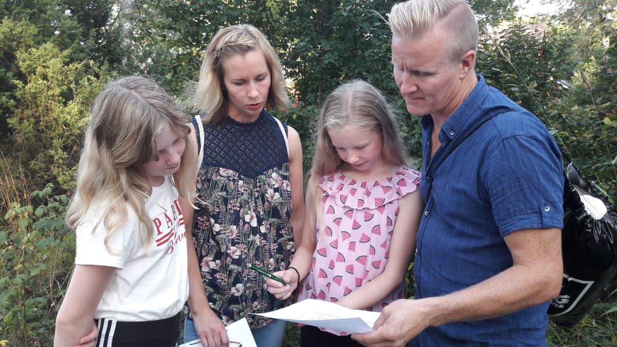 Isä, äiti ja kaksi tytärtä lukevat paperia