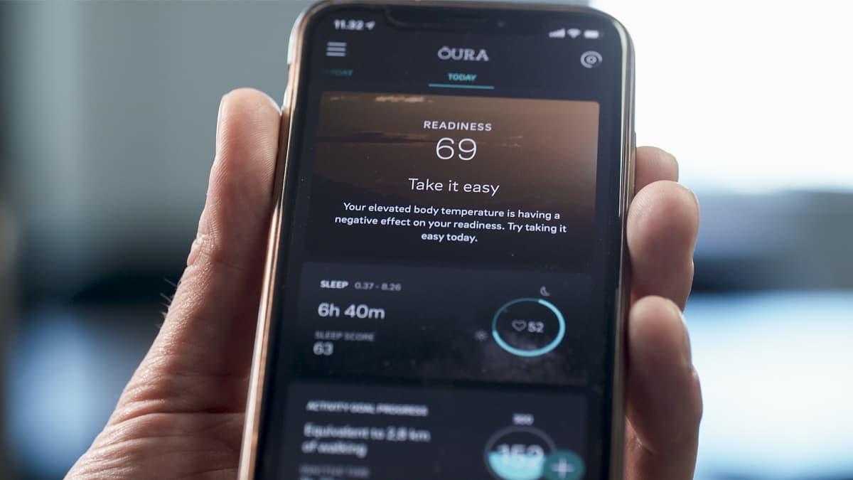 Oura Healthin sovelluksen valmius-näkymä  (readiness) miehen kädessä olevan älypuhelimen näytöllä.