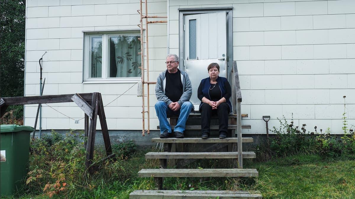 Leena ja Ismo Kilpeläinen istuvat talon portailla.