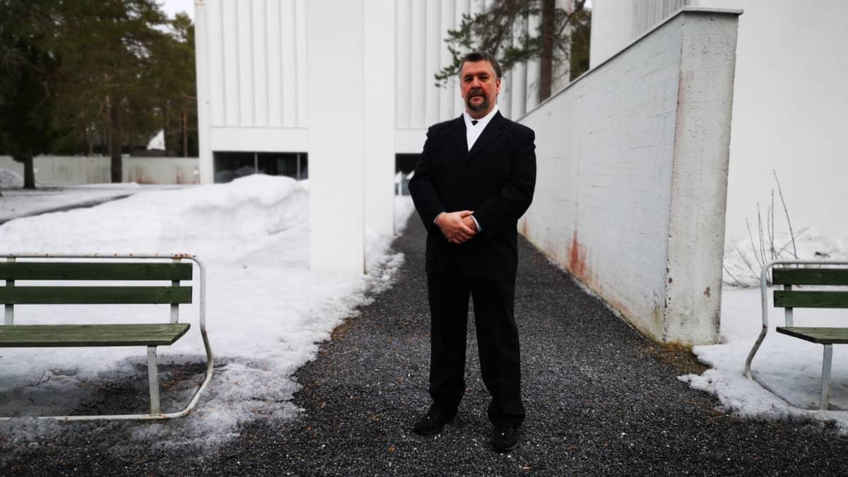 Veijo Kirkinen seisoo kappelin edessä.
