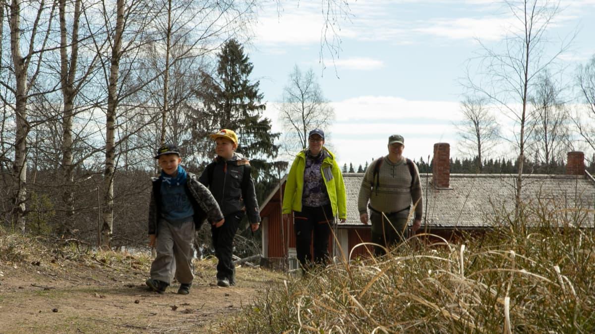 Mies, nainen ja kaksi poikaa kävelevät luonnossa.