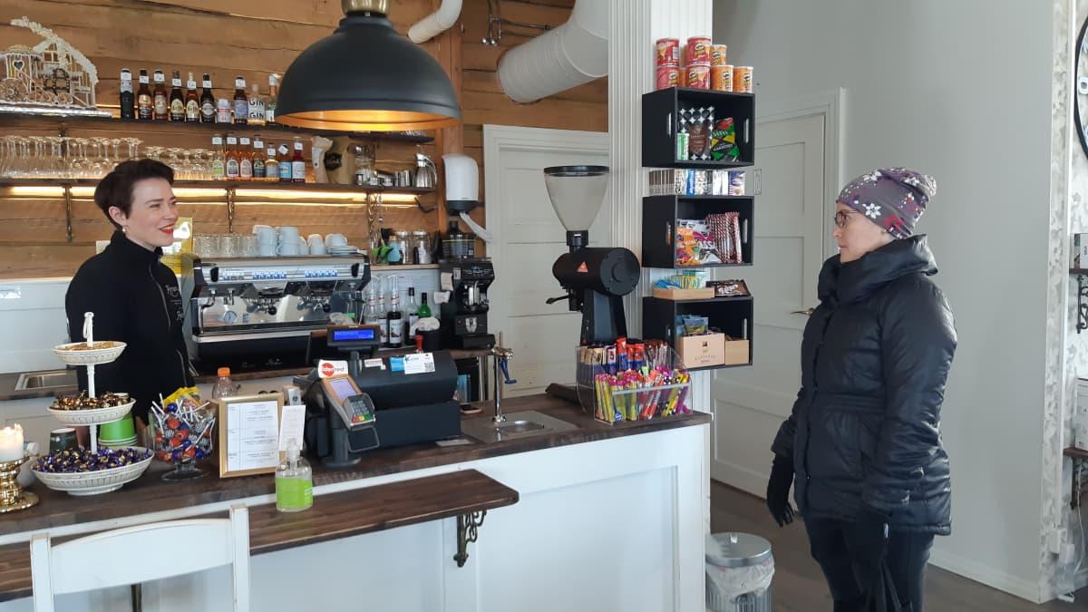 Kemiläisen Café Hertan yrittäjä Katariina Seppälä seisoo tiskin takana, asiakkaana Pia Salmela.