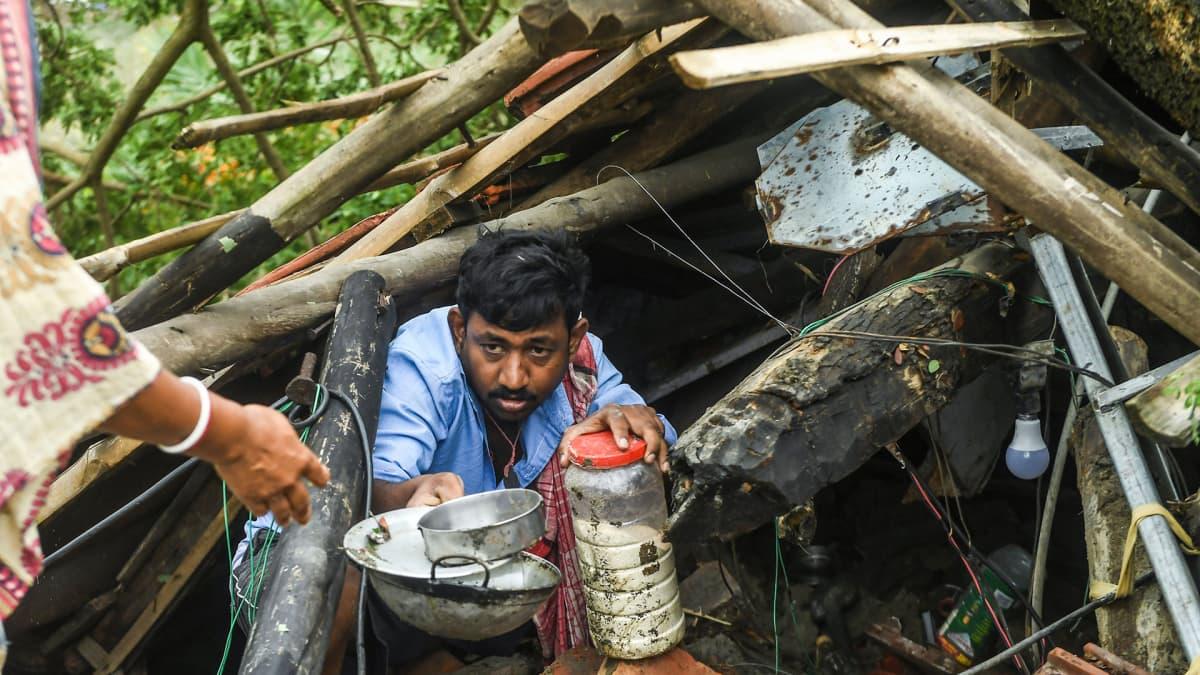 Mies pelastaa esineitä tuhoutuneen kotinsa raunioista..