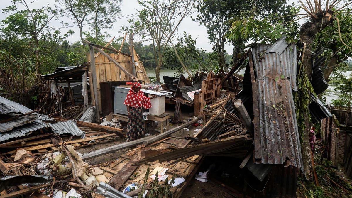 Nainen seisoo tuhoutuneen kotinsa raunioilla.