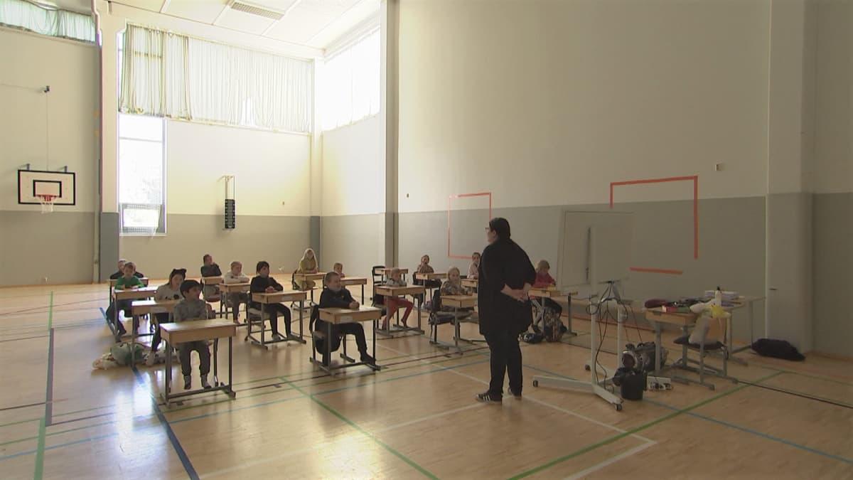Oppilaat istuvat väljästi pulpettiensa takana liikuntasaliin järjestetyssä luokassa Peltosaaren koululla Riihimäellä.