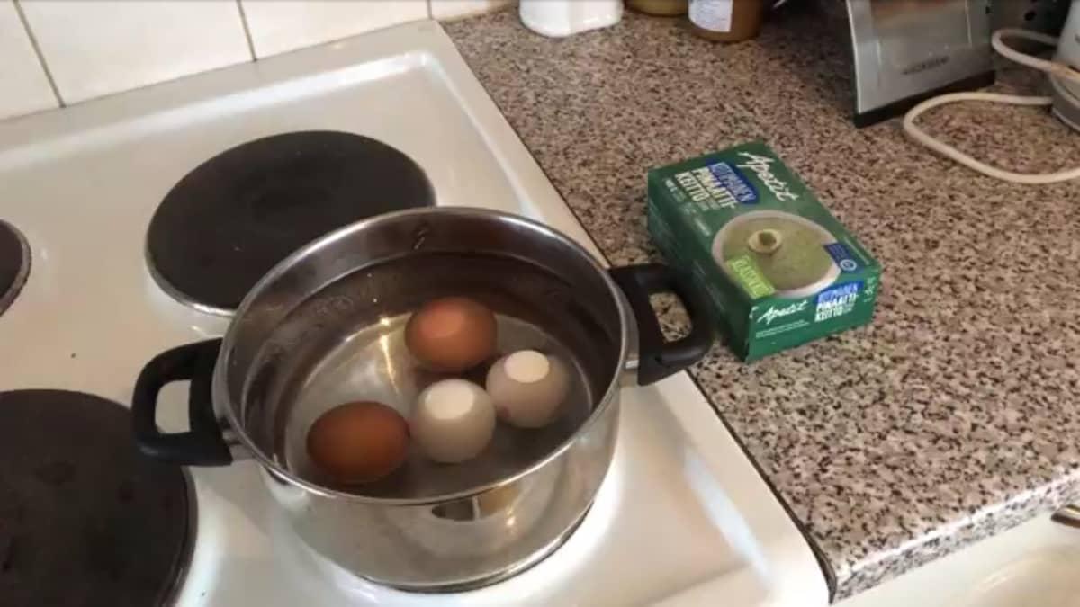 Neljä kananmunaa kattilassa ja vieressä pyödällä pakaste pinaattikeitto paketti.