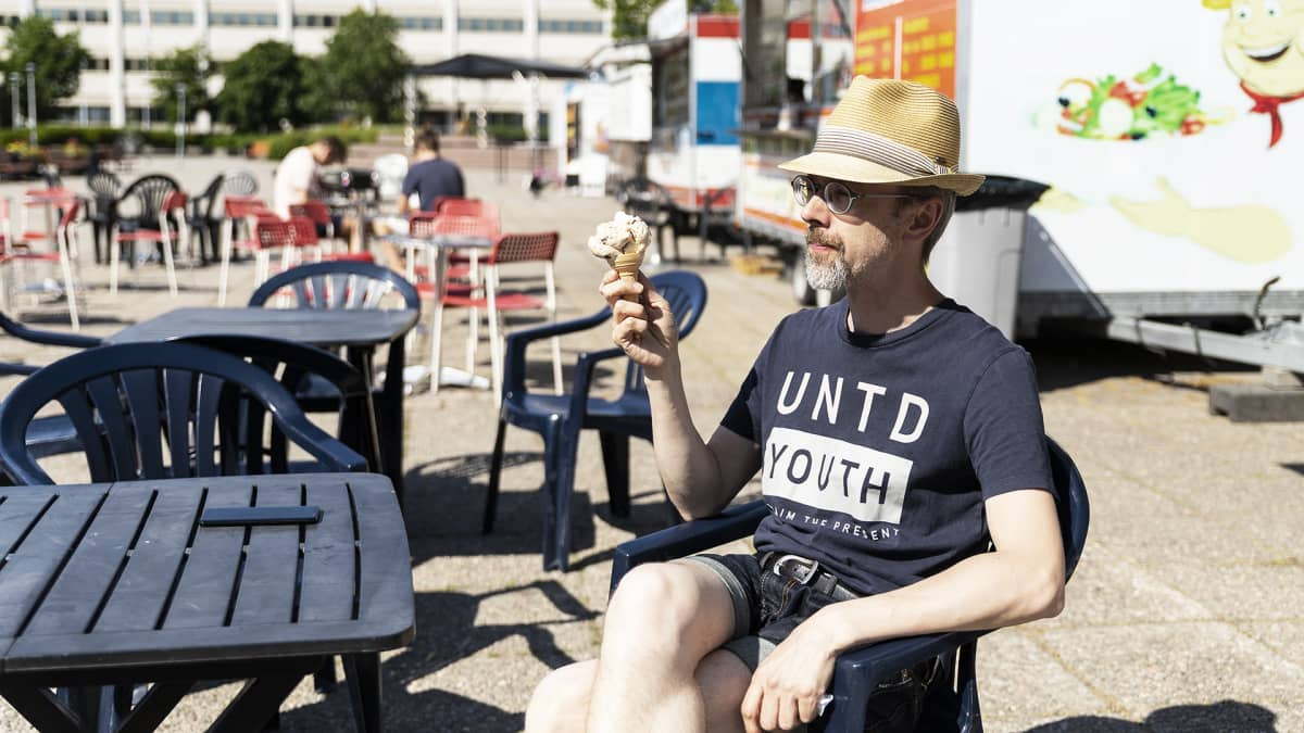 Mies syö jäätelöä torilla