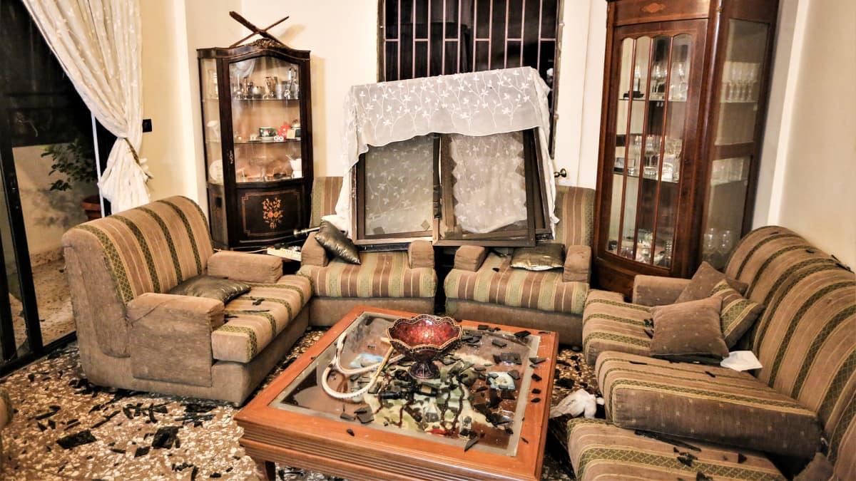 Kuva talon sisältä räjähdyksen vaikutuksista. Ikkunat rikkoutuneet räjähdyksen voimasta ja huone täynnä sirpaleita.