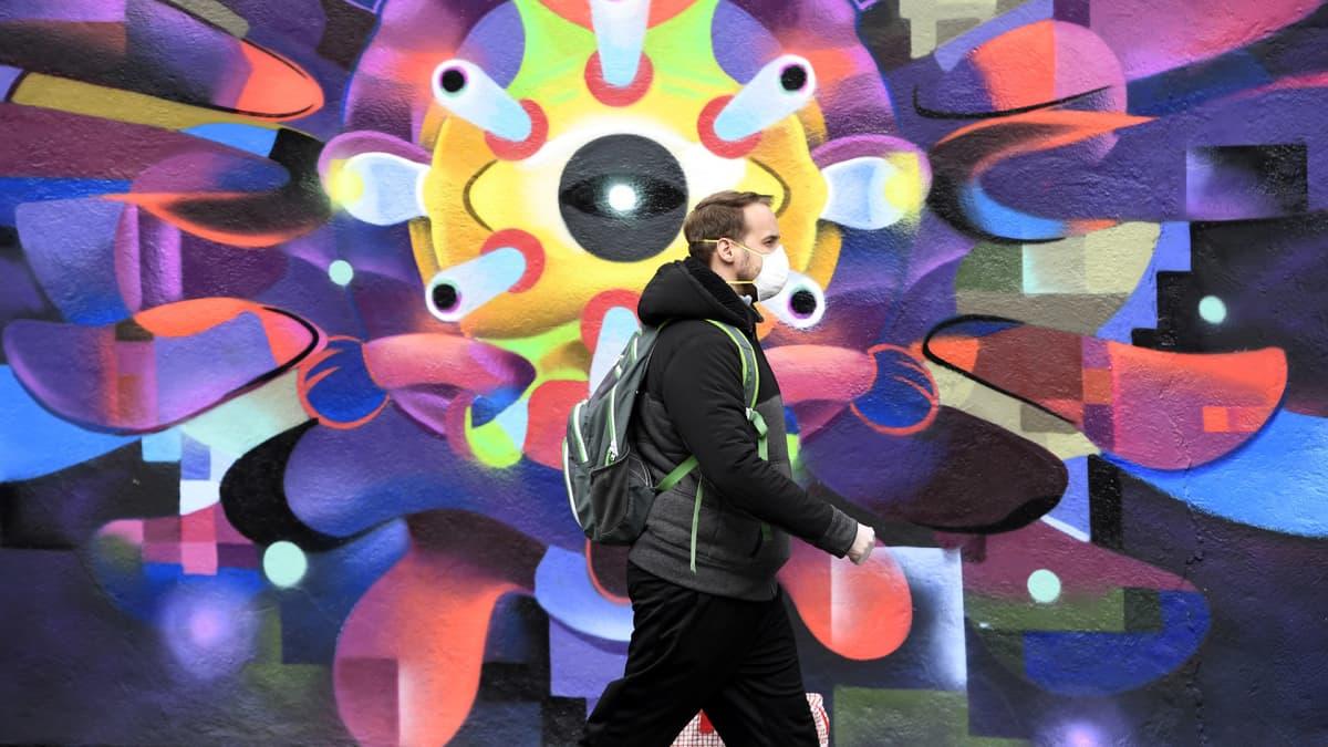 Mies kävelee Dublinissa koronavirusta esittävän muraalin ohi.