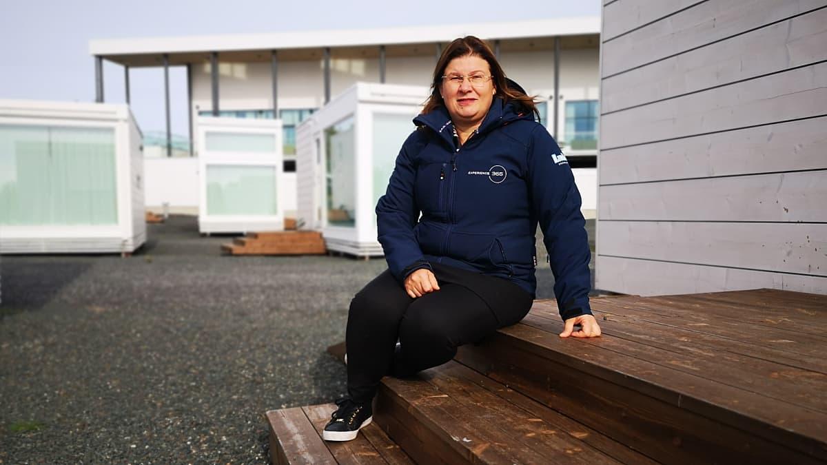 Kemin Matkailun toimitusjohtaja Susanna Koutonen istuu lumilinna-alueen lasivillan portailla.