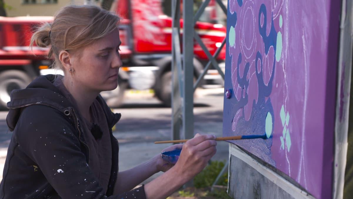 Kuvataiteilija Julia Sand maalaa sähkökaappia. Käpylän 100-vuotisjuhlatempaus: sähkökaappeihin kuvia Kalevalasta.