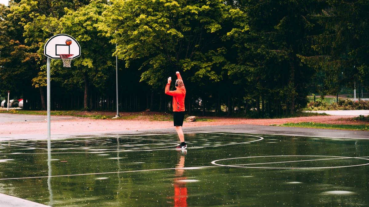 Mies heittää koripalloa tyhjällä kentällä.