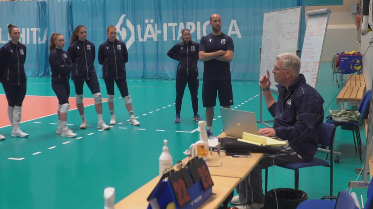 Jim McLaughlin puhuu, Tapio Kangasniemi ja Suomen naisten lentopallomaajoukkue kuuntelee.