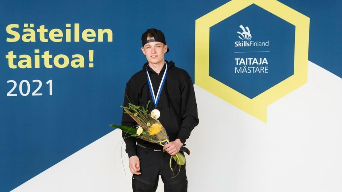 Taitaja-kisassa putkiasennuksen kultaa voittanut opiskelija Veikka Röyttä katsoo kameraan kädessään kukkakimppu.