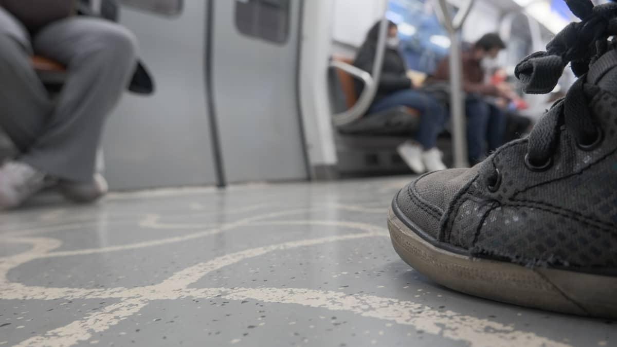 Metrovaunu kuvattuna niin, että lähellä istuvista näkyvät vain jalat ja kauempana on hämäriä ihmishahmoja.