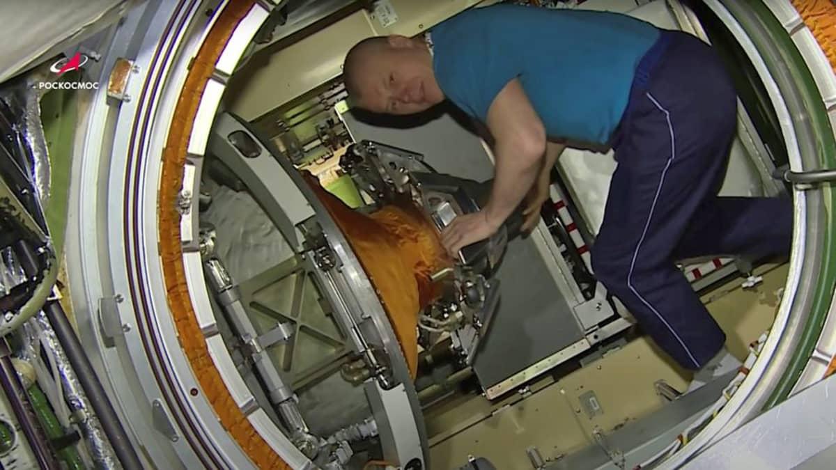 Veryttelyhousuihin ja T-paitaan pukeutunut mies kumarassa laitteiden täyttämässä tilassa.
