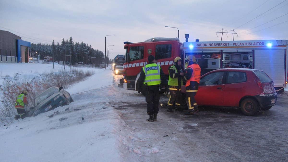 Kuvassa onnettomuusautot, joista toinen ojassa, toinen tiellä. Lisäksi  paloauto, poliiseja ja palomies.