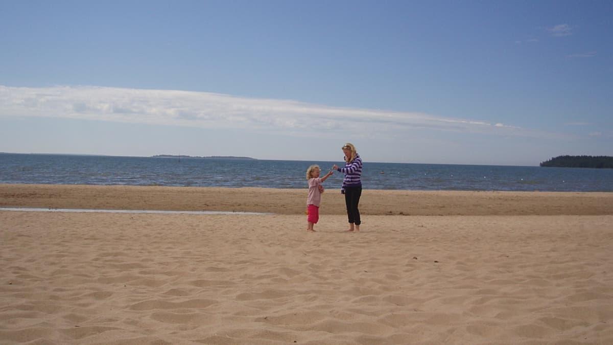 Nainen ja lapsi Yyterin hiekkarannalla.
