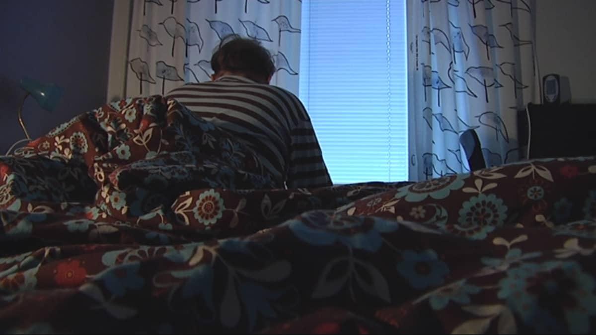 Masentunut mies istuu sängyllä