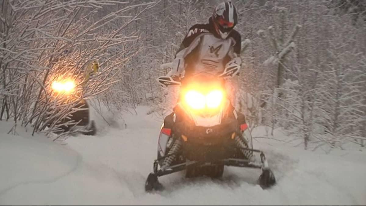 Moottorikelkkoja lumisessa säässä.