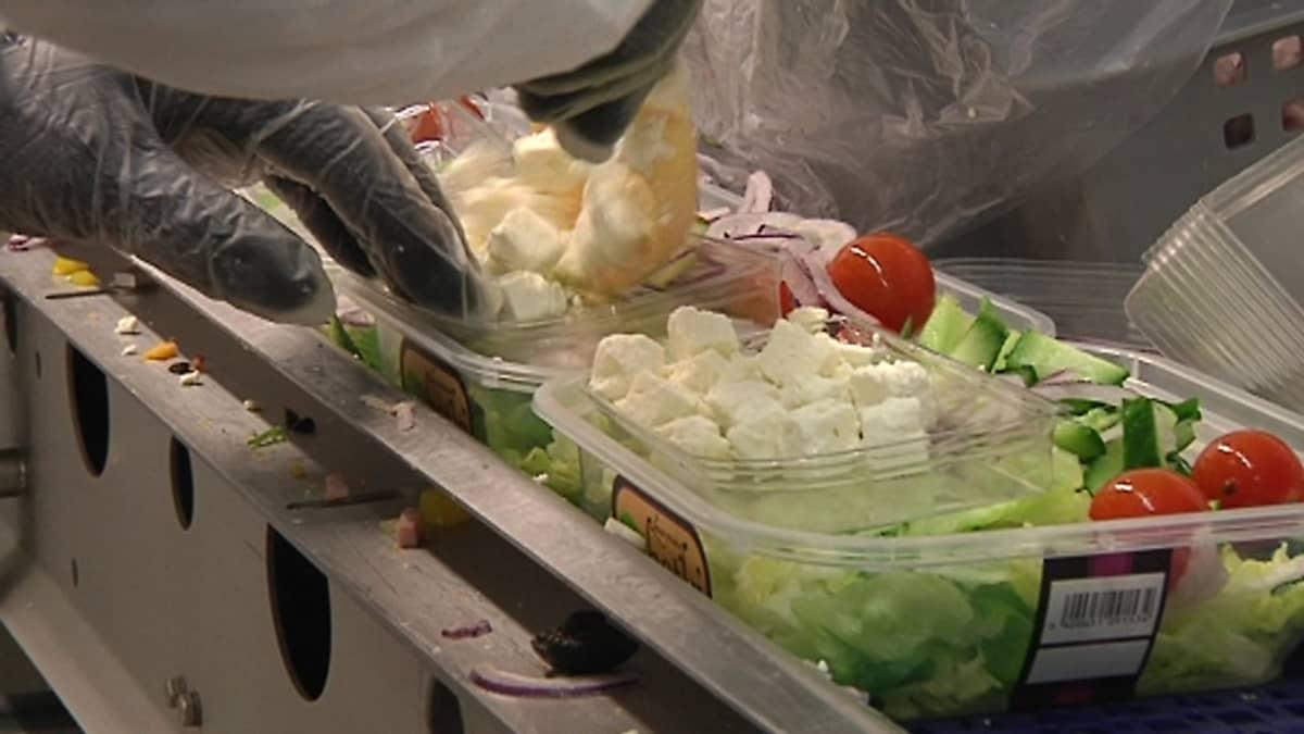 Kuvassa kumihansikoitu työntekijä kokoaa muovisiin salaattirasioihin kreikkalaisen salaatin ainesosia