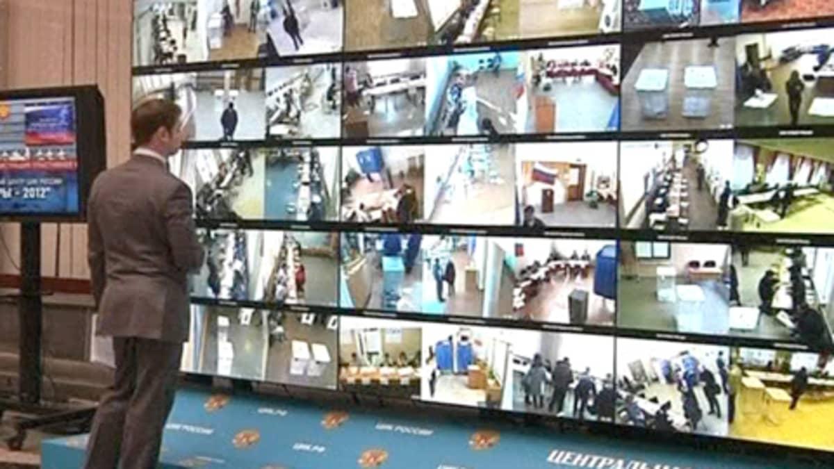Mies katselee valvontakamerakuvia Venäjän vaalien äänestyspaikoilta.