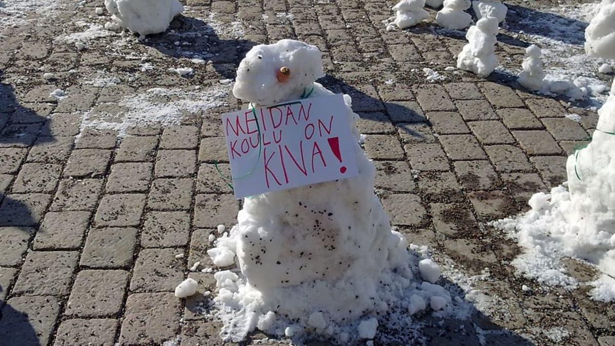Lumiukko osoittaa mieltä paperilappu kaulassa Kotkan torilla