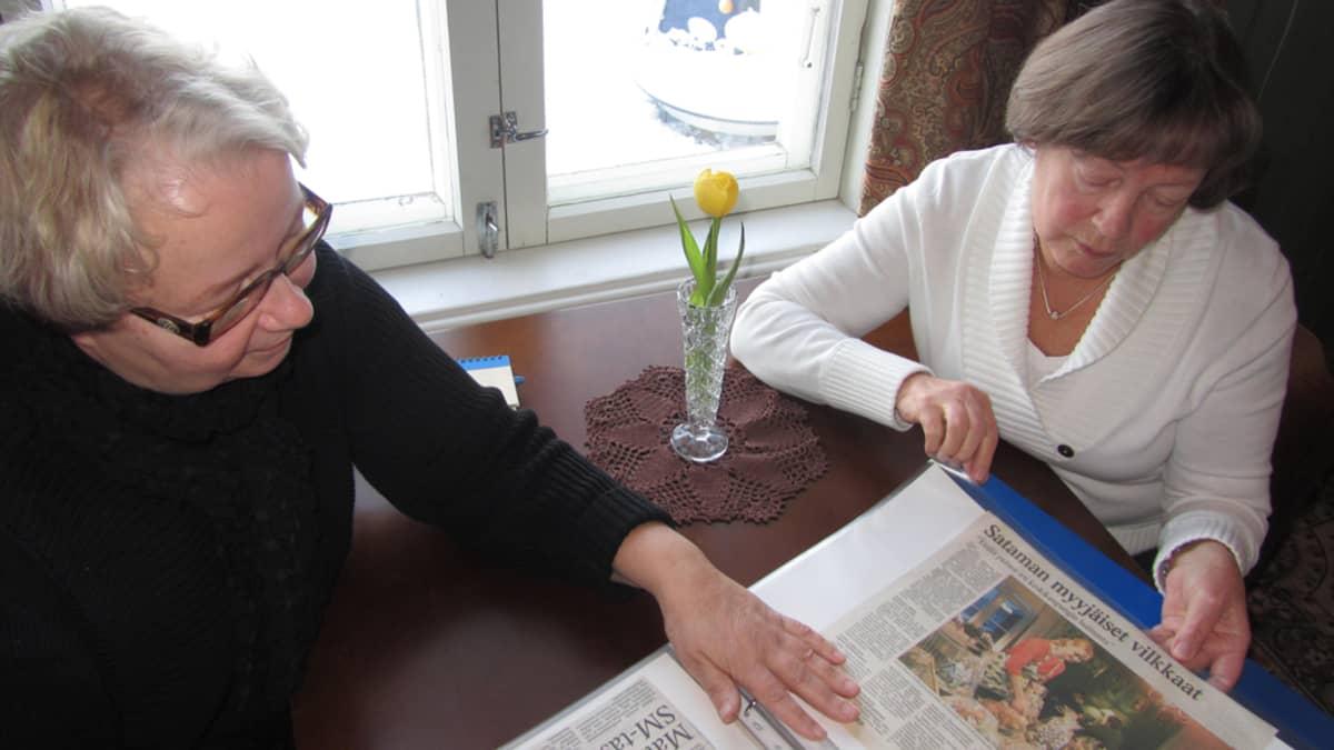 Anja Vilen ja Sirkka Laaksonen selailevat leikekirjaa kahvilassa.