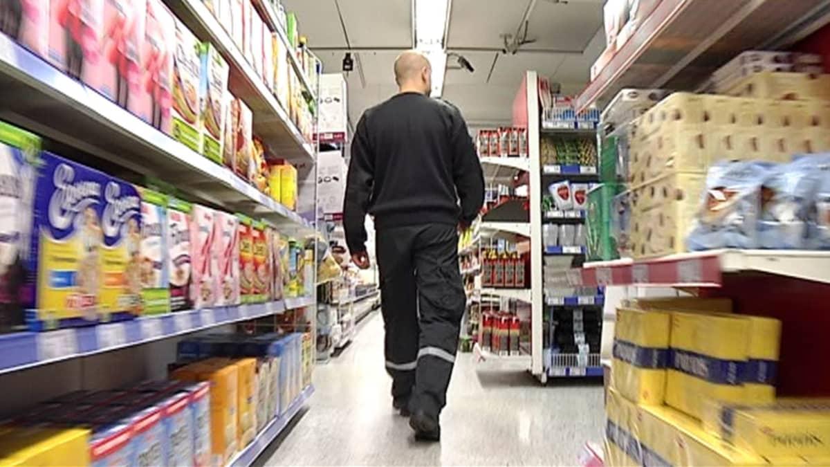 Vartija kävelee ruokakaupan hyllyjen välissä.