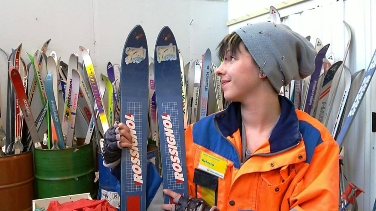 Rebekka esittelee käytettyjä suksia Oulun kierrätyskeskuksen myymälässä.