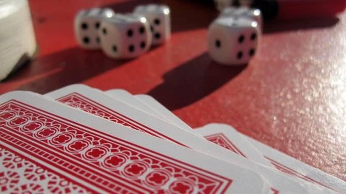 Korttipakka ja nopat pöydällä.