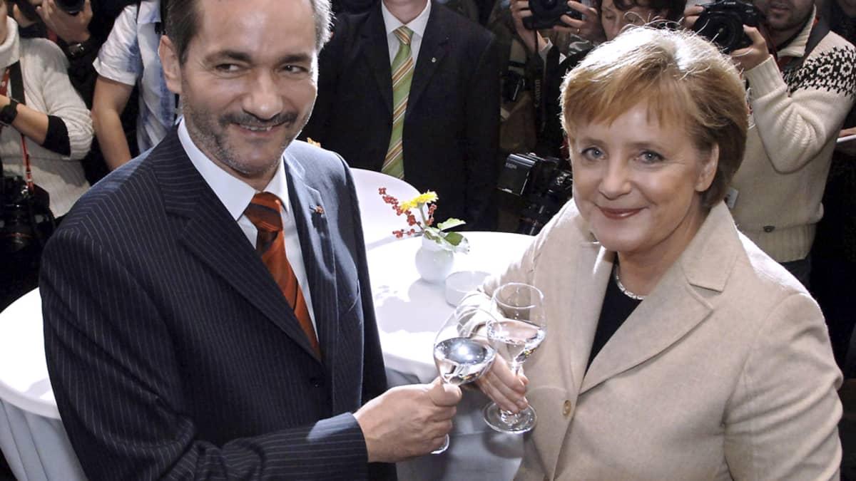 Tuolloinen sosiaalidemokraattisen puolueen puheenjohtaja Matthias Platzeck ja Angela Merkel skoolaavat vaalivoiton kunniaksi 18.5.2005.