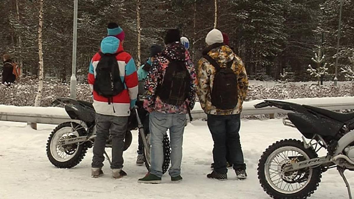 Pojat seisovat mopon edessä.