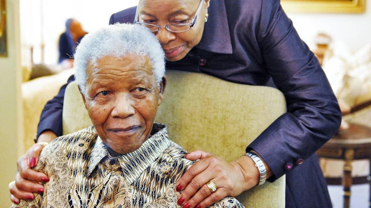 Mandela istuu tuolissa, Machel kumartuneena pitelee hänen olkapäistään kiinni.