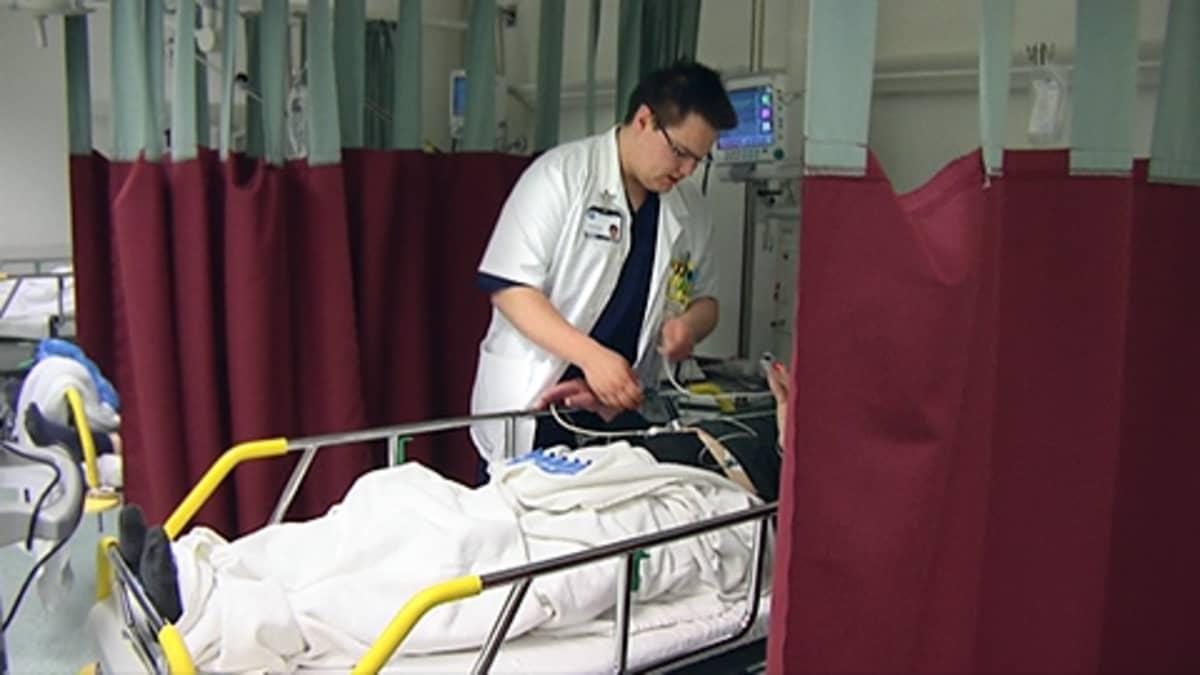 Sairaanhoitaja potilaan luona Acutassa.